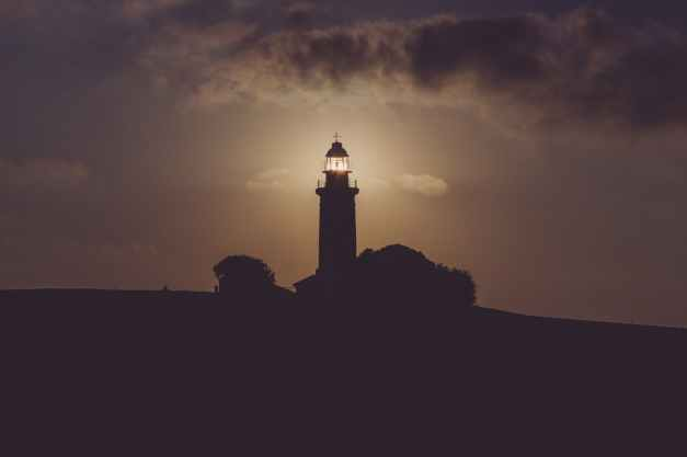 silhouette of light house under gray dark sky
